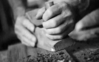 mani di un falegname che sta piallando un'asse di legno