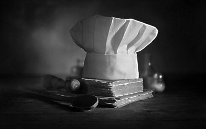 Un cappello da cuoco sopra un libro di cucina