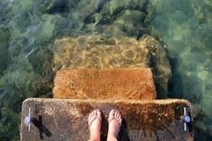 Un paio di piedi in bilico su un gradino in bilico sul mare