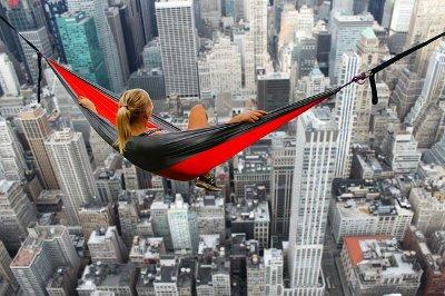 donna su un amaca sospesa sopra una città piena di grattacieli