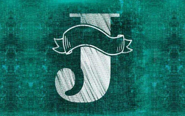 La lettera J disegnata con il gesso bianco su uno sfondo verde