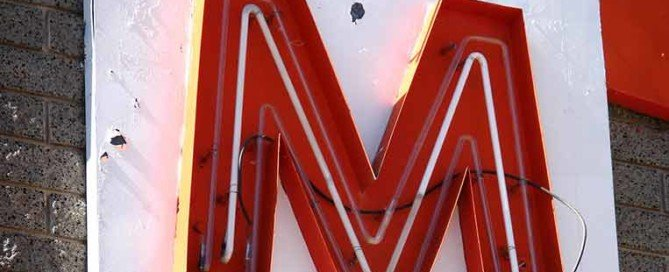 La lettera M come insegna rossa su un muro bianco