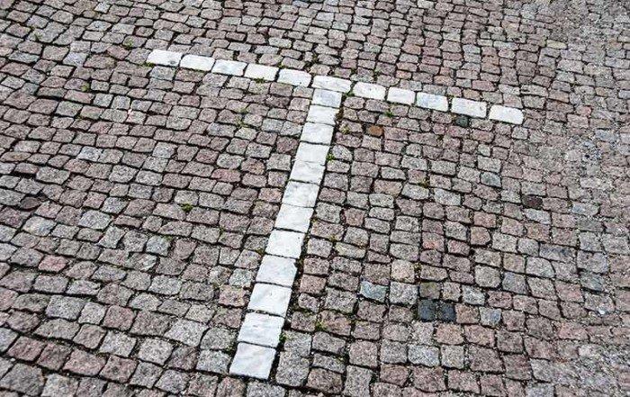 La lettera T disegnata con i sampietrini bianchi incastonati in una strada