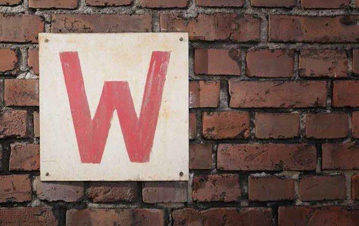 Cartello bianco, con all'interno una lettera W rossa, attaccato su un muro di mattoni