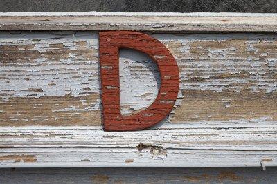 La lettera D in colore rosso attaccata su un'asse di legno
