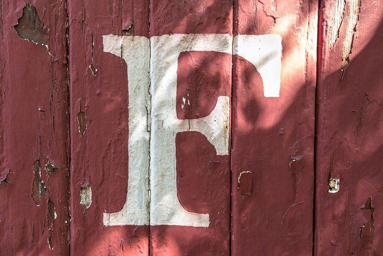 La lettera F bianca dipinta su un muro rosso